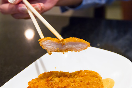 breaded pork chop: chopsticks with breaded pork on white dish