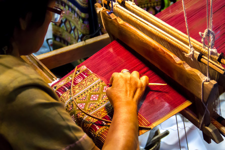 People are silk weaving in Thailand photo
