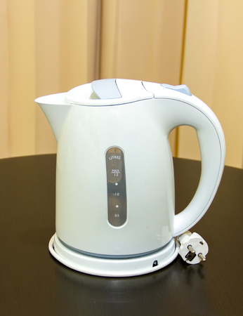 Electric kettle placed on a wooden table photo