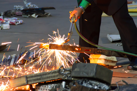 acetylene: A worker uses a oxygen acetylene cutting torch to cut scrap at twilight