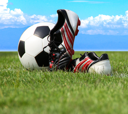 football shoes: Football shoes and a football on green grass and blue sky