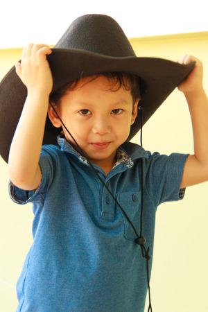 Little boy wearing a black cowboy hat photo
