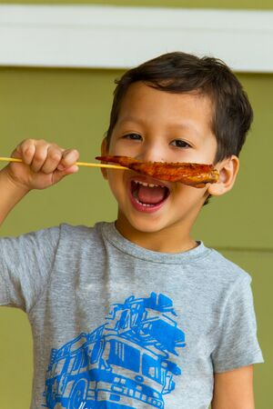 Boy happy with eating grilled chicken Stock Photo