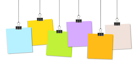 Empty coloured papers with binder clips hanging at black twine