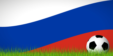 soccer ball lying in the grass in front of russian flag