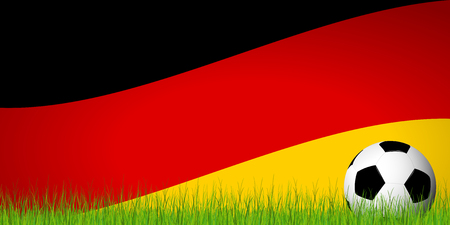 Soccer ball lying in the grass in front of german flag