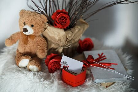 A bear with rose flowers on white skin on which a gift certificate in a box. A gift for Valentines Day