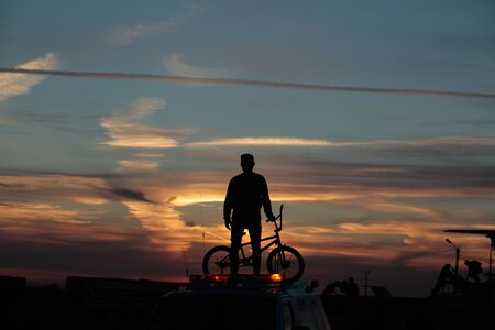 Cyclist on sunset background. Ski jumping competitions