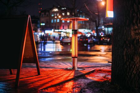 Street heater with a beautiful red light and bokeh in the form of a city street
