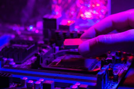 Motherboard in neon light. A hand inserts a processor into a socket on the motherboard. Computer service.