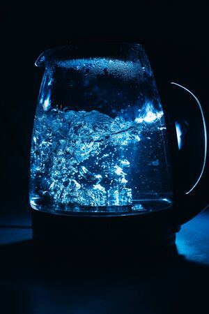 Boiling glass black teapot with blue backlight on a black background. Boiling water. Hot water is seething. Bubbles of air in the water.