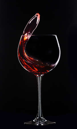 Large glass with red wine on a black background. Splashes of wine. 版權商用圖片