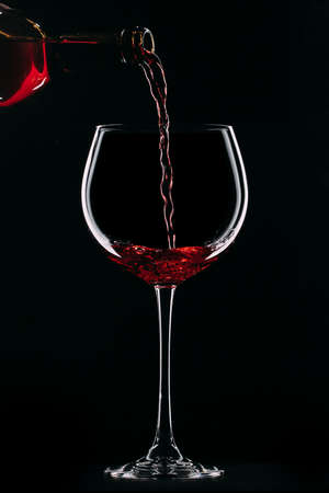 A glass filled with red wine from a bottle. Wine glass on a black background.
