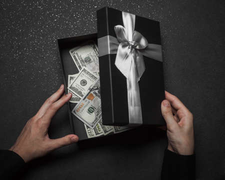 The hands of a guy in a black shirt open a gift box with a large silver bow. Money box. Granite background.