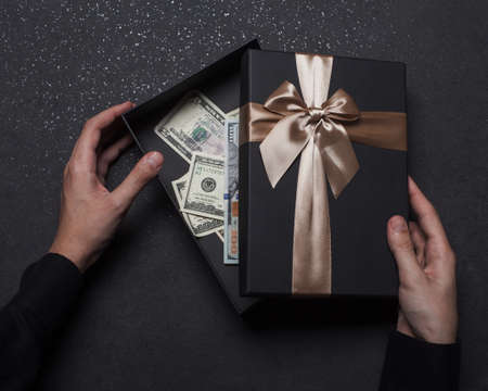 The hands of a guy in a black shirt open a gift box with a large golden bow. Money box. Granite background.