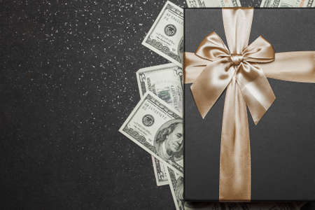 Black gift box with gold ribbon and a big bow on a pile of money. Gift on a granite surface.