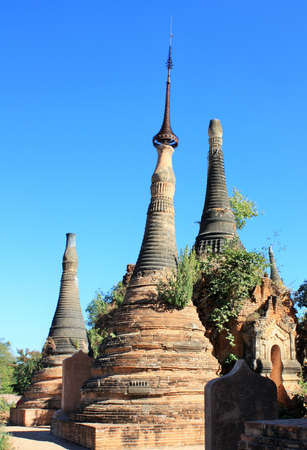 Ruins of old stone pagodas with green plants growing on them at In Dien located on the southwestern side of Inle Lake, Myanmar