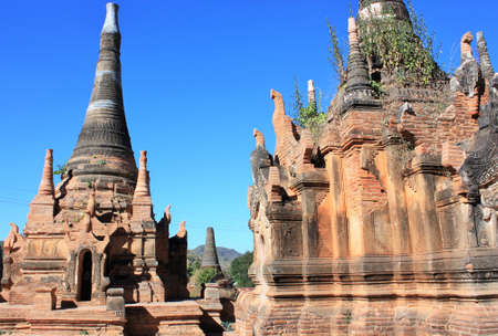 Old stone pagodas with green plants growing out of them at In Dien located on the southwestern side of Inle Lake, Myanmar 스톡 콘텐츠