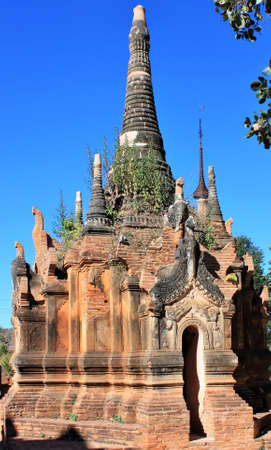 Ruins of an old stone pagoda with green plants growing out of it at In Dien located on the southwestern side of Inle Lake, Myanmar 스톡 콘텐츠