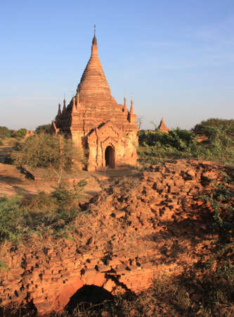 Ruins of a Pagoda surrounded by green plants at sunset in Bagan, Myanmar