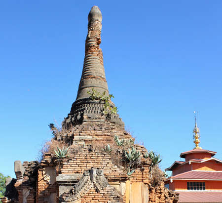 Ruins of an old stone pagoda with green plants growing out of it next to a modern temple structure at In Dien located on the southwestern side of Inle Lake, Myanmar