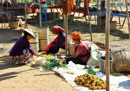 Inle Lake, Shan State / Myanmar - December 18, 2019: Local Pa'O ethnic people wearing traditional clothes at a vegetable stall at Phaung Daw Oo market