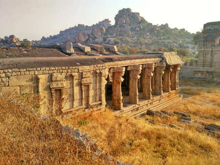 Wall and columns of ruins in Achyuta Raya Temple Complex at sunrise with rocky hill in background in Hampi, Karnataka, India