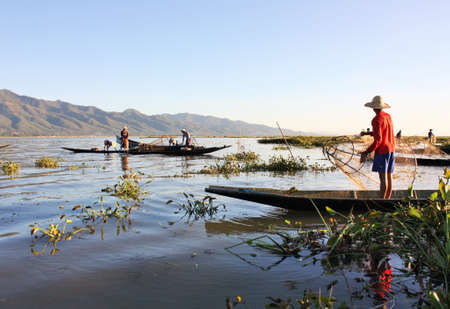 Burmese fishermen standing in small boats among green plants while fishing with nets at Inle Lake, Shan State, Myanmar