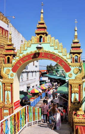 Tourists and religious pilgrims walking under a gateway arch near Kyaiktiyo Pagoda (Golden Rock), Mon State, Myanmar