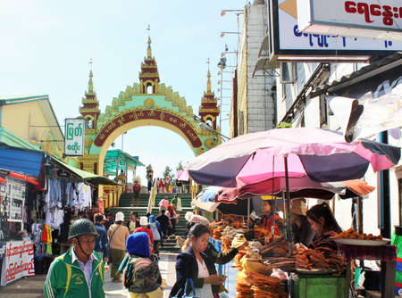 Tourists and religious pilgrims walking under a gateway arch and shopping at food stalls near Kyaiktiyo Pagoda (Golden Rock)