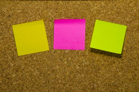 3 colours stick note isolated on cork board background Stock Photo - 20893652