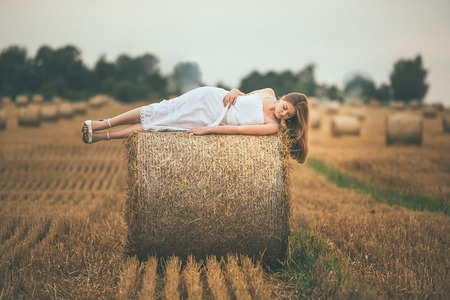 Beautiful Girl on Hay Bales in the Fields Stock Photo