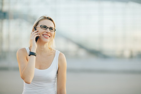 Stylish business lady in glasses talking on the phone and smiling