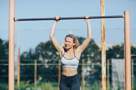 Fitness woman tightening on a turnstile Stock Photo