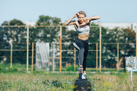 Sports girl runs and jumps over obstacles Stock Photo