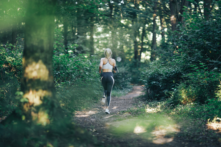 Attractive blonde, fitness woman running in the morning forest