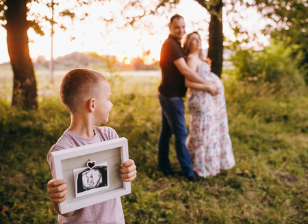 Happy young family in the park at sunset