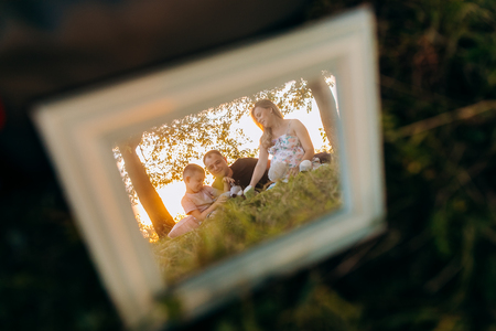 Frame with family photo on grass Stockfoto