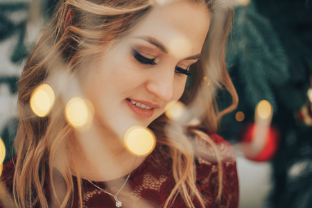 Young beautiful smiles woman through the lights of the garland Stock Photo