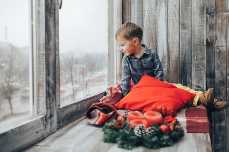 Boy sitting and looking at the window Waiting for Christmas