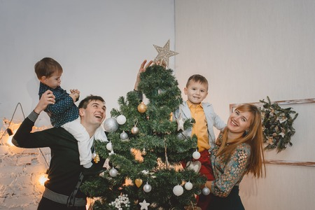 Parents and two son decorate the Christmas tree indoors. The morning before Xmas. Loving family close up. Banco de Imagens