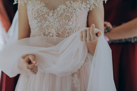 Morning preparations. Woman putting on dress. Gorgeous, blonde bride in pink luxury dress