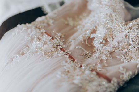 Bride in pink dress. Pink luxury dress is getting ready for wedding. Morning preparations