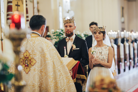 Newlyweds in the church. Priest celebrate wedding mass at the church 스톡 콘텐츠