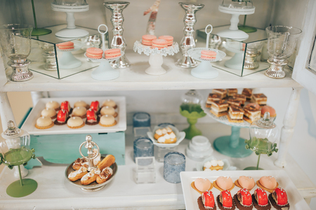 Candy bar with a lot of cookies and fruits. Chocolate fountain and wedding cake