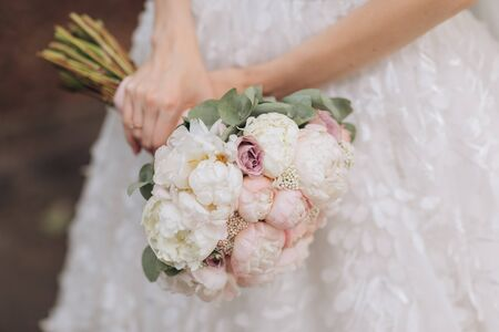 Closeup of a bride in white dress holding her wedding bouquet.