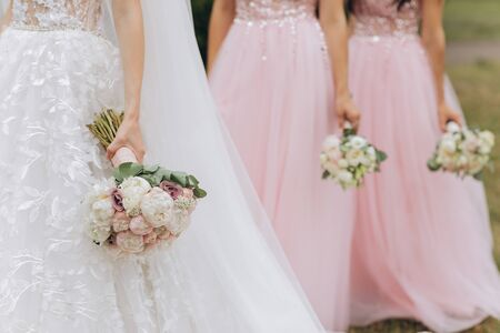 Row of bridesmaids with bouquets at wedding ceremony. Three bridesmaids holding wedding bouquets. Bride With Bridesmaids Outdoors At Wedding