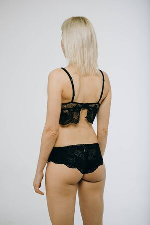 Sensual woman wearing black lingerie posing.