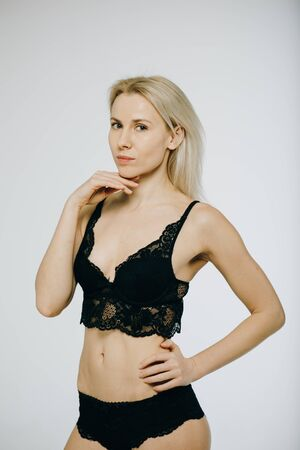 Sensual blonde beautiful woman posing in elegant black lingerie, looking at camera. White background.