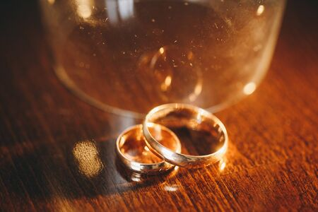 Golden wedding rings. Two golden wedding rings isolated on the table, wedding rings background concept.
